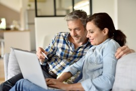 Couple in sofa websurfing and shopping on internet