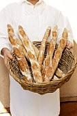 Baker holding basket with fresh baguettes