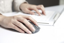 Female hands on a computer keyboard and mouse