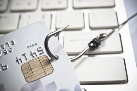hand holding a credit card with a fish hook – phishing