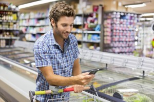 Cheerful man using app mobile phone in store. Shopping list.Texting