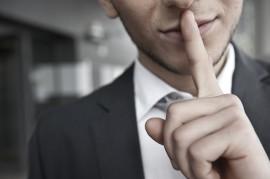 mann mit anzug legt finger auf lippen