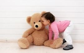 Ein Kleinkind spielt mit seinem Teddybren