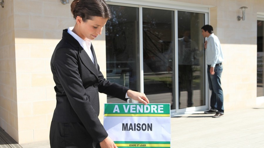 Woman placing home for sale sign